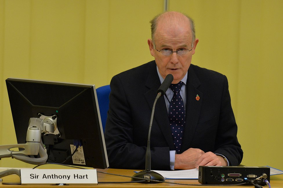 Sir Anthony Hart sits at a desk during the Historical Institutional Abuse Inquiry