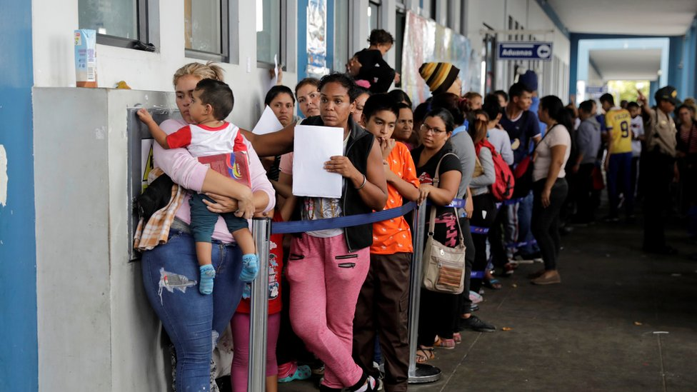 Venezuelans queue outside an immigration office in Tumbes, Peru