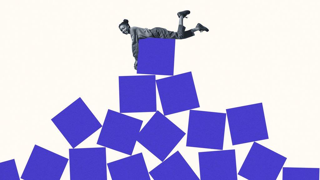 Chica encima de una pirámide de cubos desorganizados
