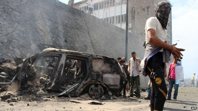 Yemenis gather around the wreckage of a car at the site of a blast that hit the convoy of the governor of Aden