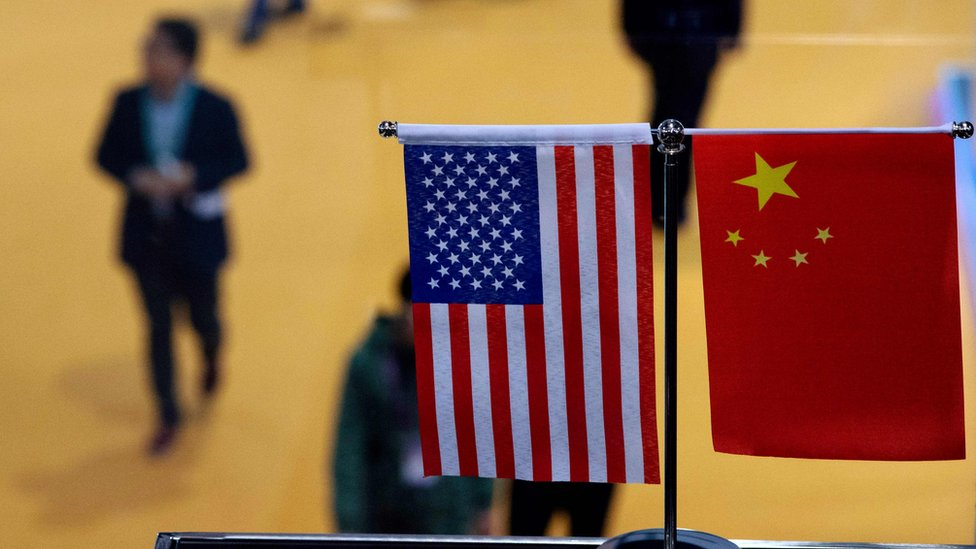 Una bandera de China y Estados Unidos se muestran una al lado de la otra en la Exposición Internacional de Importaciones de China (CIIE) en Shanghai, noviembre de 2018.