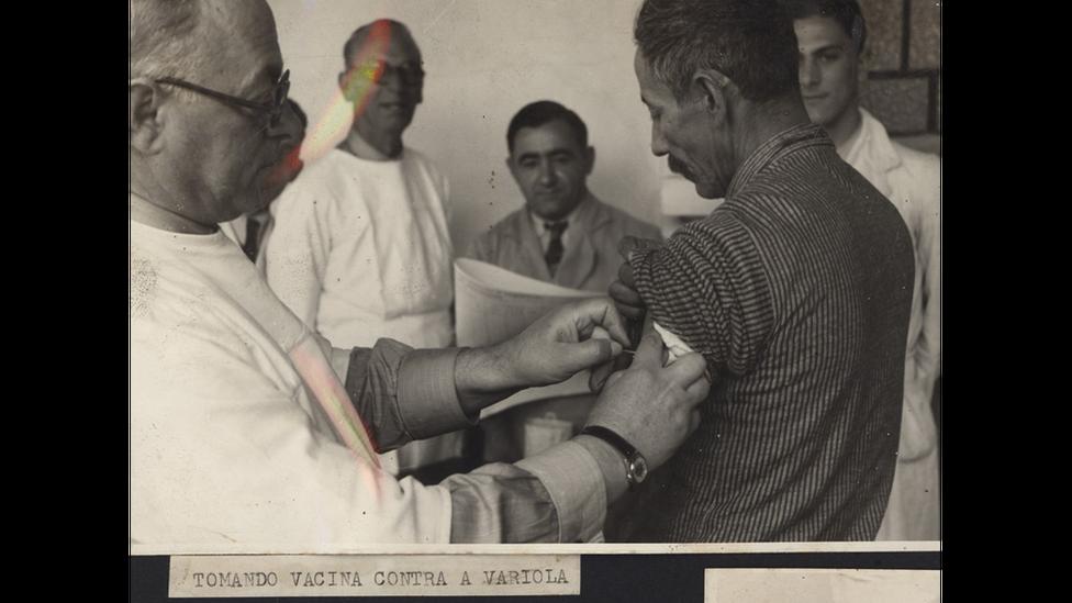 Foto em preto e branco mostra homem, de costas, sendo vacinado por outro homem em sala