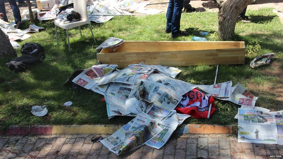The body of a victim, covered by newspapers, lies next to a coffin after an explosion in Suruc, Turkey (20 July 2015)
