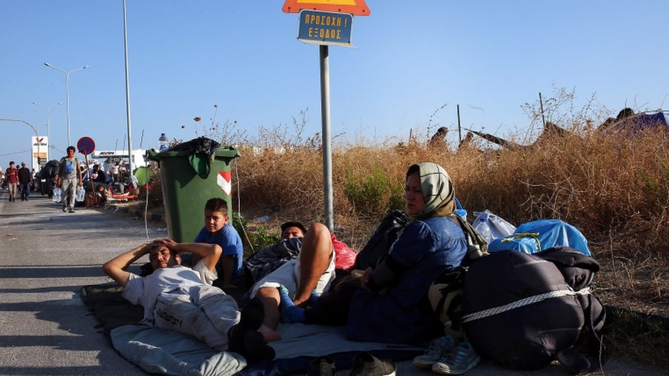 Migrants sit by the roadside near the camp site