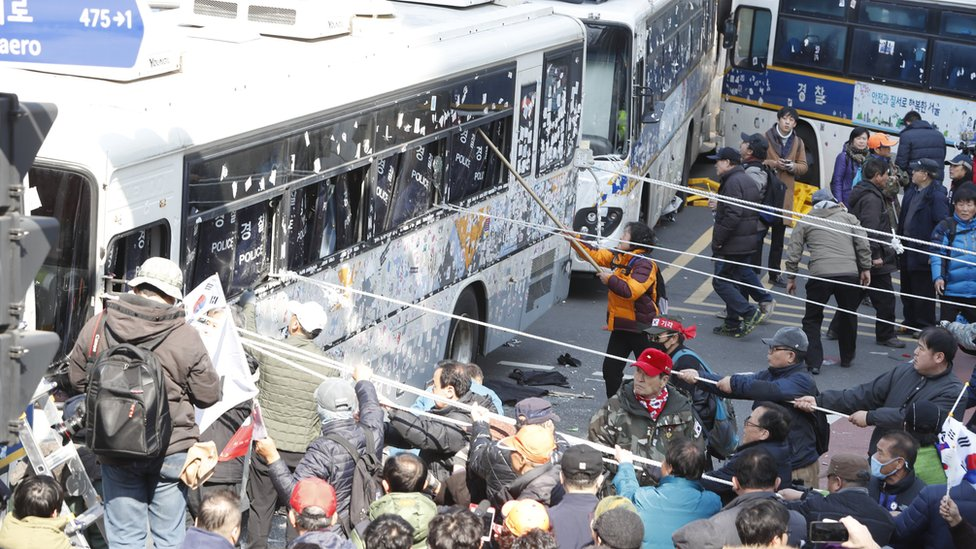 Supporters of impeached South Korean President Park Geun-hye clash with police as they attempt to pass a barricade of police buses near the Constitutional Court in Seoul, 10 March 2017