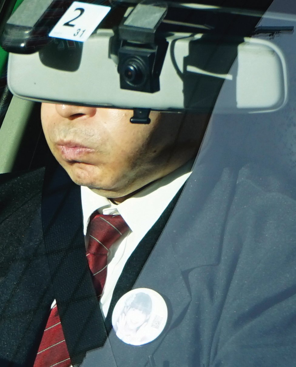 A taxi driver's eyes are covered by a windscreen mirror