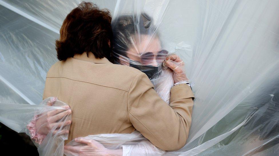 أوليفيا غرانت تحتضن جدتها عبر فاصل بلاستيكي في نيويورك في 24 مايو/أيار
