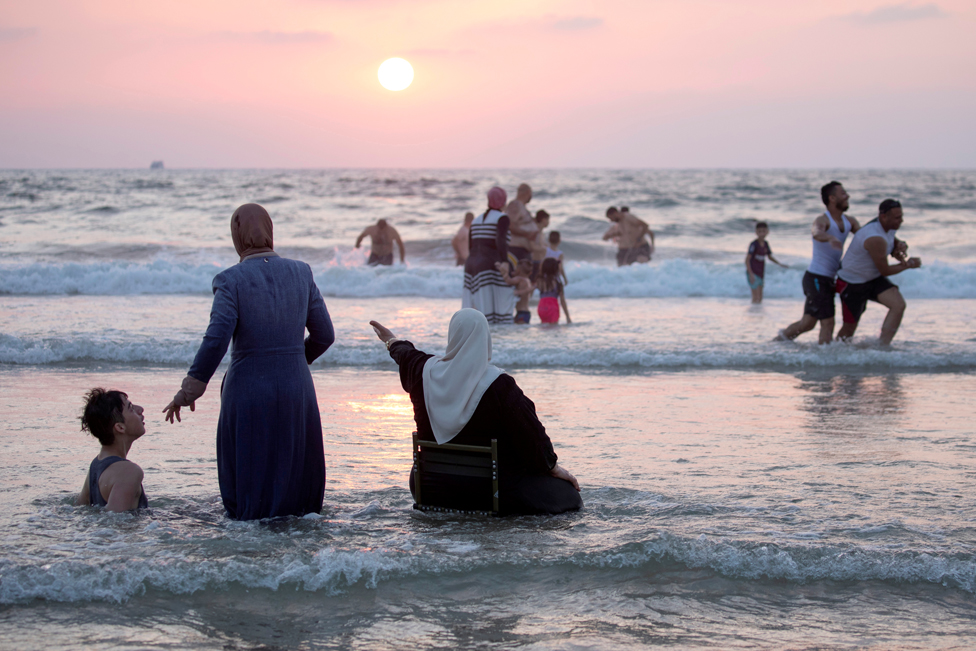 People enjoy themselves in the Mediterranean Sea during Eid al-Adha, in Tel Aviv, Israel