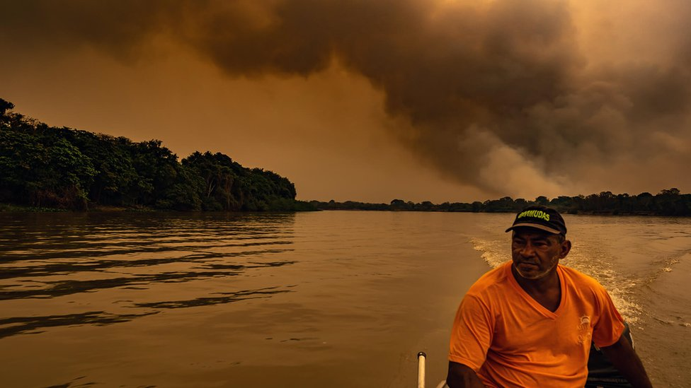 A man on his boat can be seen in the darkness caused by the wildfires
