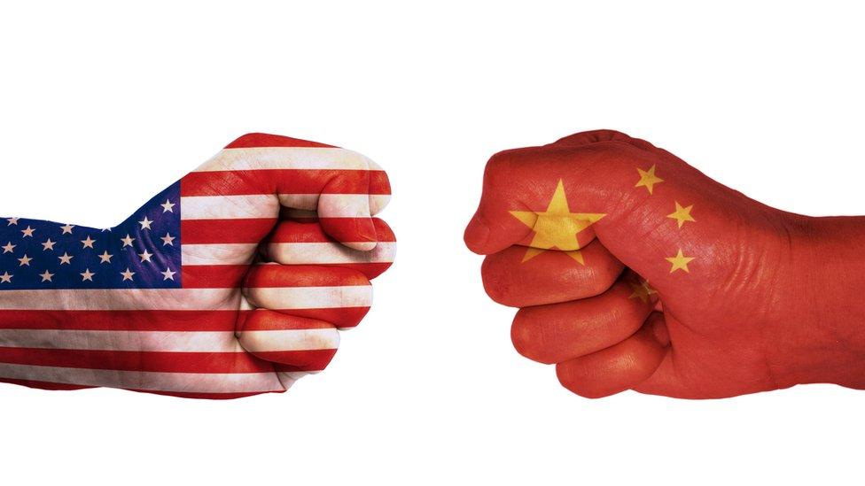Diseño con manos pintadas con abnderas de EEUU y China.