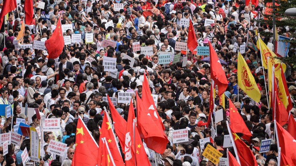 Pro-Beijing demonstrators shout slogans and wave flags outside the Hong Kong Legislative Council on November 13, 2016