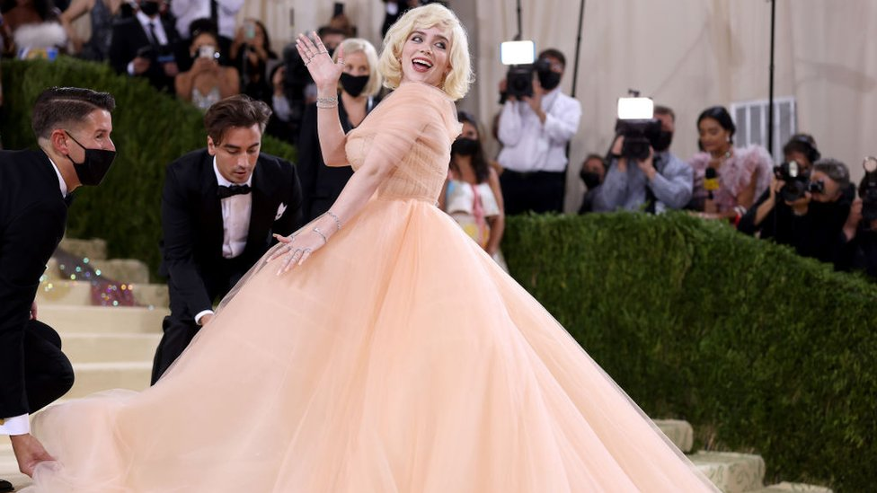 Billie Eilish waves to the crowd in a peach outfit that drew comparisons with Marilyn Monroe