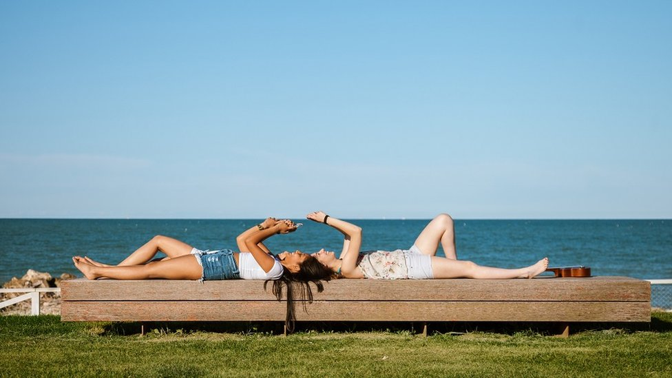 Girls lying down on a bench, by the sea, texting