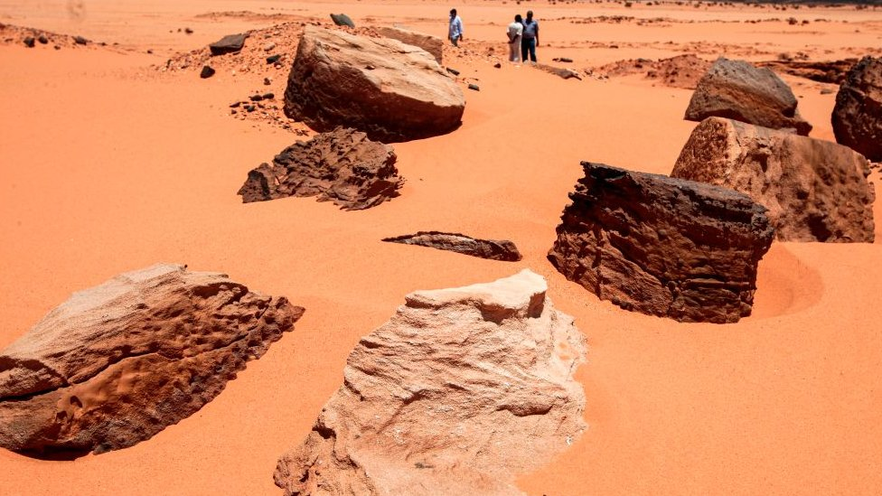 Remains of the two millenia-old site of Jabal Maragha that was ravaged by gold hunters are scattered on the sand in the desert of Bayouda,