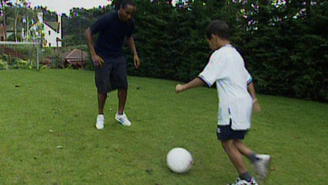 Paul Ince and Tom Ince play football in garden