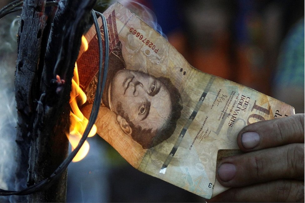 A man burns a 100-bolivar bill during a protest in El Pinal, Venezuela December 16, 2016.