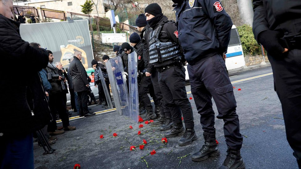 Flowers are placed next to Turkish police officers as they stand guard near the Reina nightclub, which was attacked by a gunman, in Istanbul, Turkey, on 1 January 2017