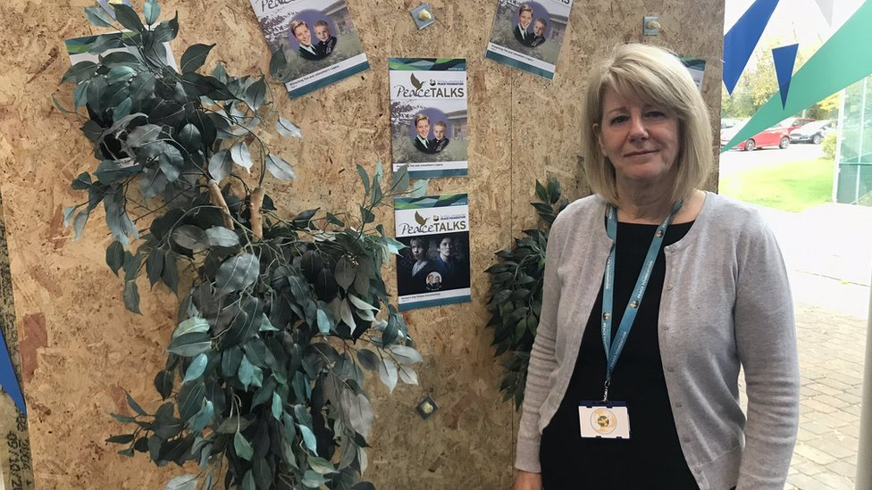 Wendy Parry, founder of the Warrington Peace Centre next to the damaged panel