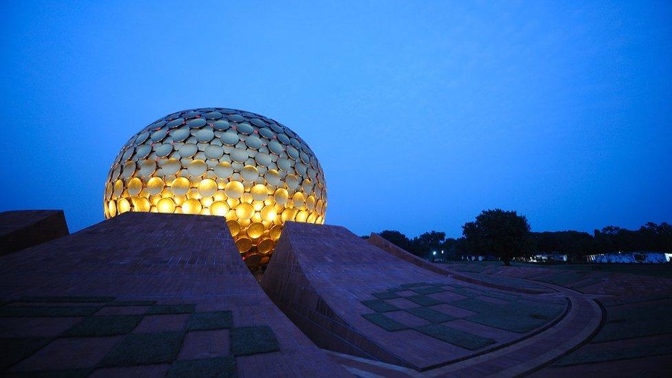 The Matrimandir at dusk: the building is a giant golden globe, over a dark blue sky.