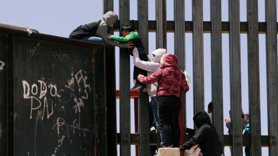 طفل صغير يمر فوق جدار حدودي في الولايات المتحدة