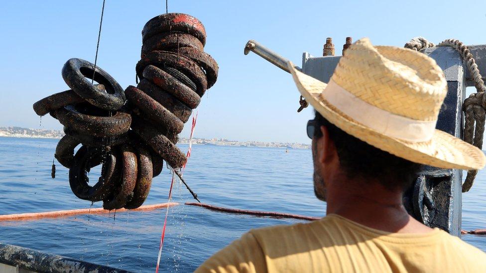 Čovek gleda kako se gume izvlače sa morskog dna