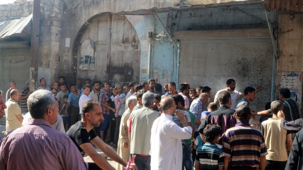 Men wait in line to receive food aid in Aleppo, Syria 10/08/2016