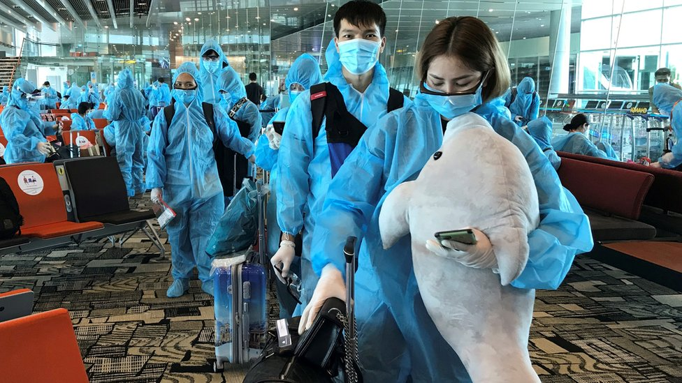 A Vietnamese woman carries a stuffed animal while boarding a repatriation flight from Singapore to Vietnam amid spread of the coronavirus disease (COVID-19) outbreak at Changi airport, Singapore August 7, 2020.