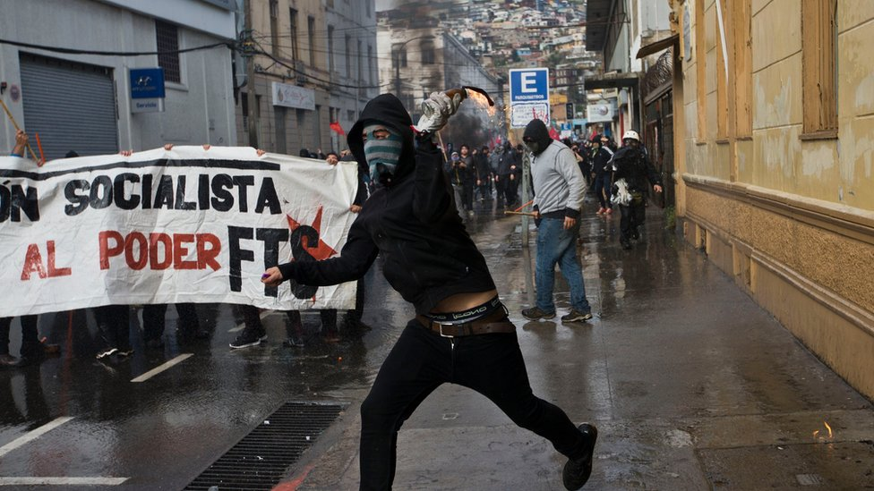 A masked protester launches a Molotov cocktail