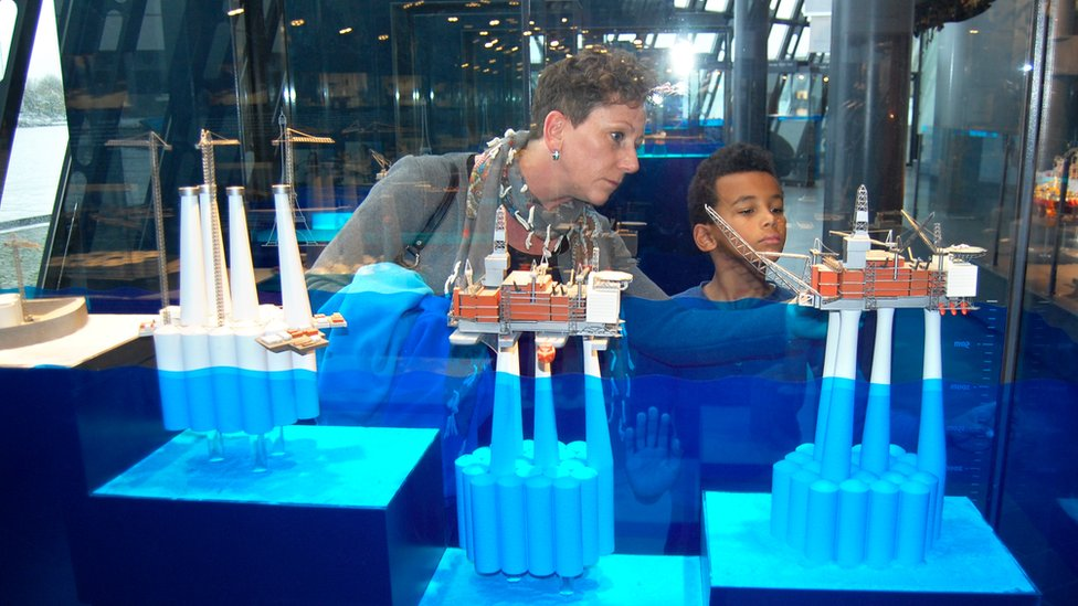 A woman shows an oil platform miniature replica to a child in Stavanger's oil museum