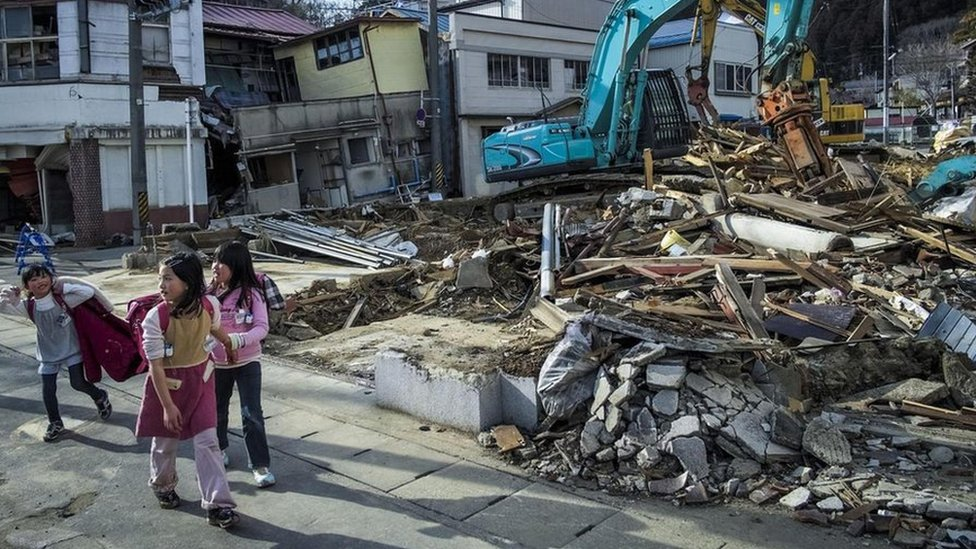 Girls walking passed a destroyed house