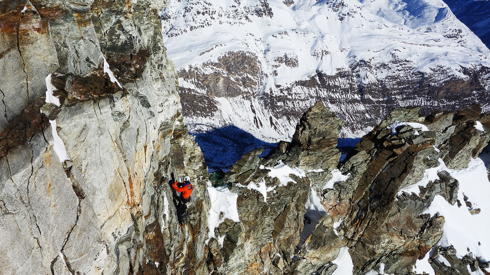 A researchers install sensors on rocks of Mount Matterhorn in the Alps