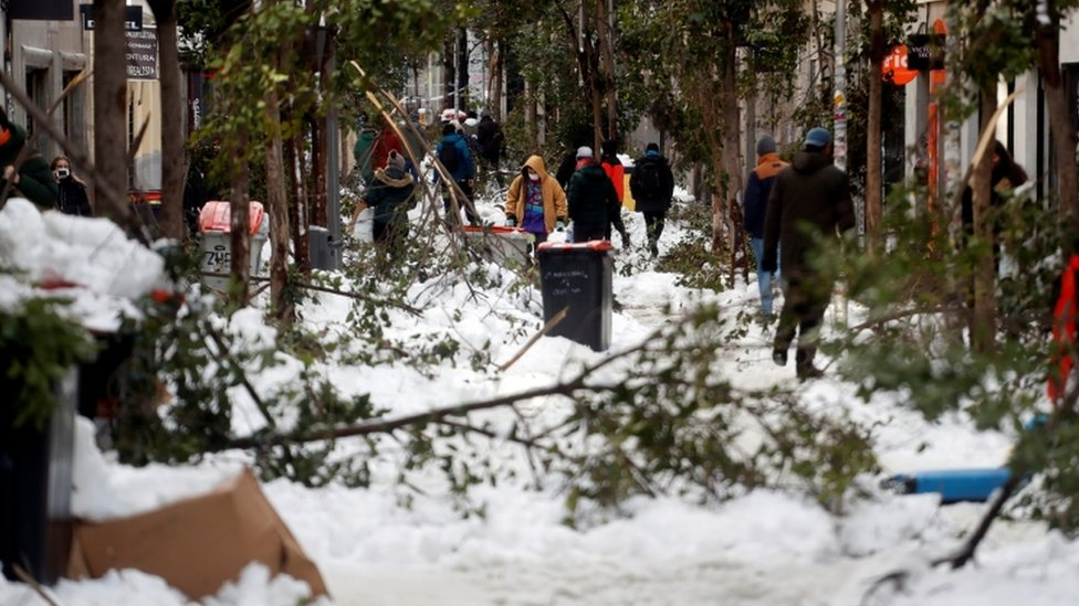 People walk through the snow and among fallen branches in Madrid, Spain January 10