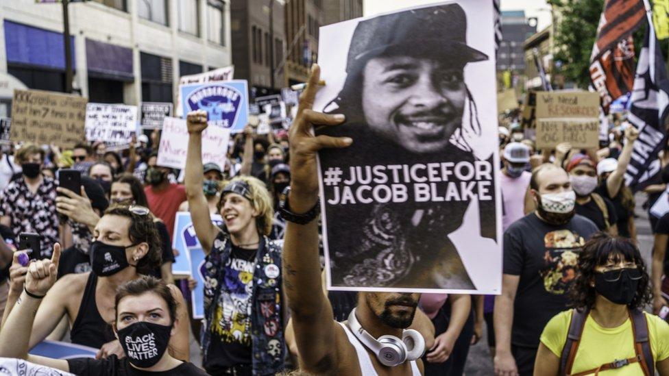明尼蘇達州明尼阿波利斯市群眾舉著威斯康辛州基諾沙市警察槍擊案傷者雅布各·布萊克(Jacob Blake)照片遊行聲援(24/8/2020)