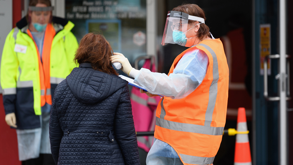 Medical worker carrying out a temperature check outside a medical centre