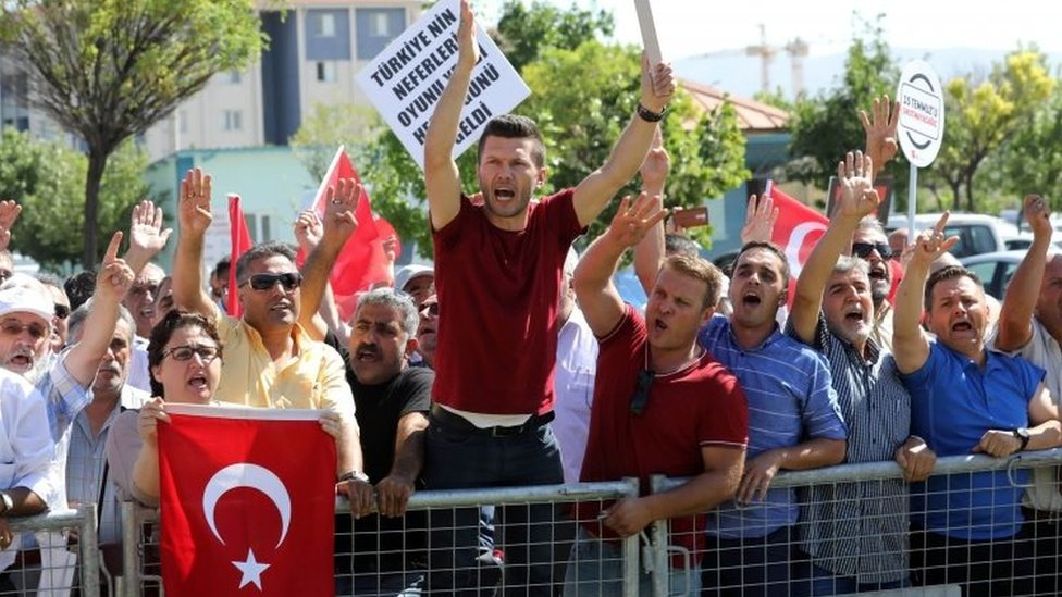 People protest against arrested soldiers who allegedly participated in last year's attempted coup as they arrive for their trial (01 August 2017)