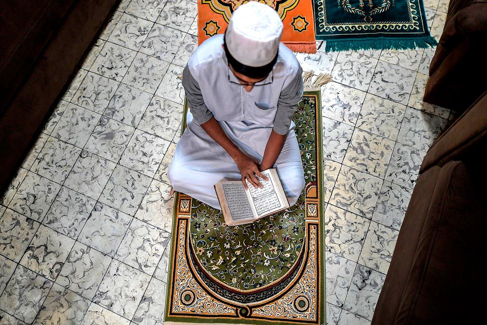 مسلم يقرأ القرآن بمنزله في بنما سيتي، عاصمة بنما، قبل الإفطار