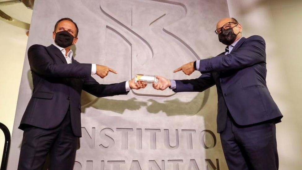 O governador de São Paulo, João Doria, e o diretor do Butantan, Dimas Covas, aparecem de máscara em frente a painel com inscrição 'Instituto Butantan' segurando juntos embalagem da Coronavac