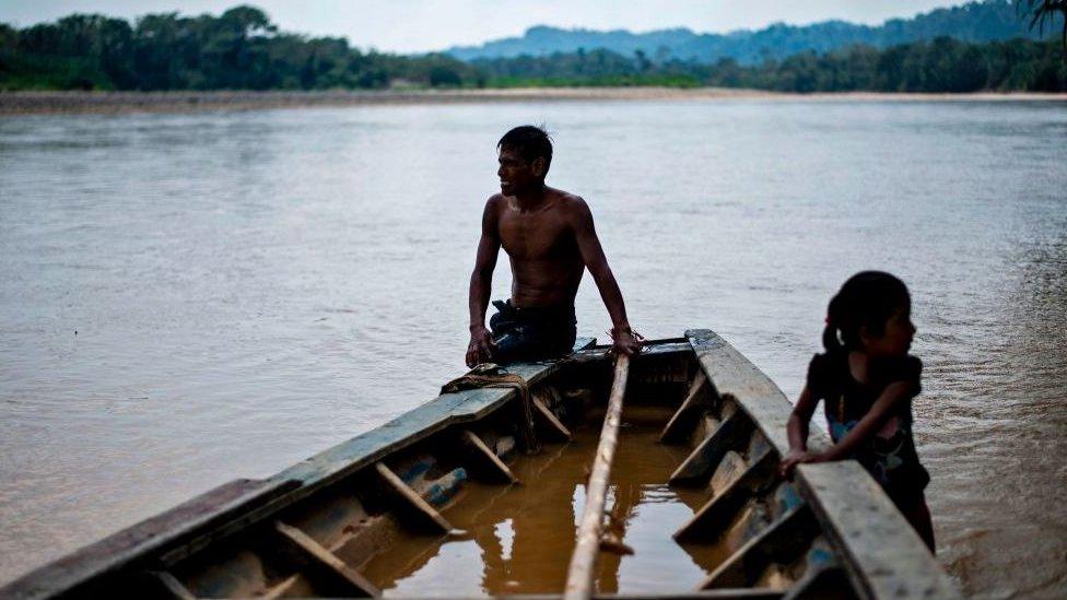 Dos niños en un bote sobre el caudaloso Amazonas