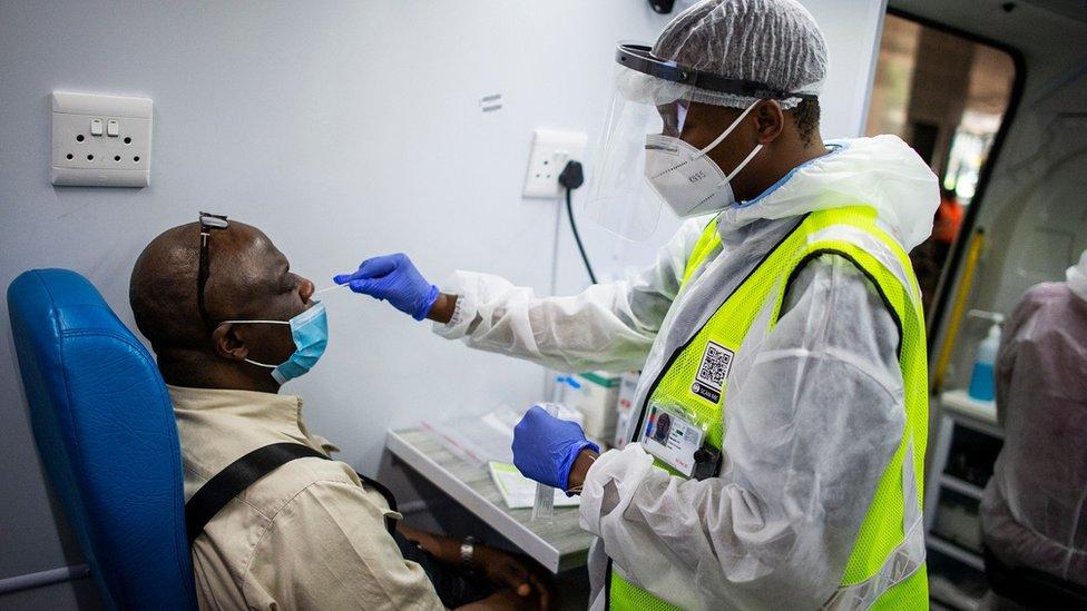 Um membro da equipe médica do Departamento de Saúde da África do Sul obtém uma amostra nasal de um passageiro em uma unidade móvel de teste no Aeroporto Internacional O.R. Tambo em Ekurhuleni em 30 de dezembro de 2020, onde os passageiros que apresentam sintomas de COVID-19 na chegada são testados