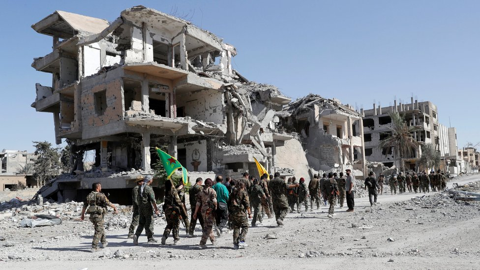 Troops from the Syrian Democratic Force (SDF) marching past a ruined building in Raqqa, Syria