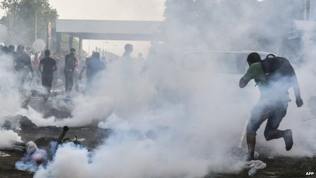 Migrants running from tear gas