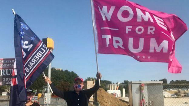 毛裏奧揮舞著兩面旗,一面藍色,另一麵粉紅色是妻子的。