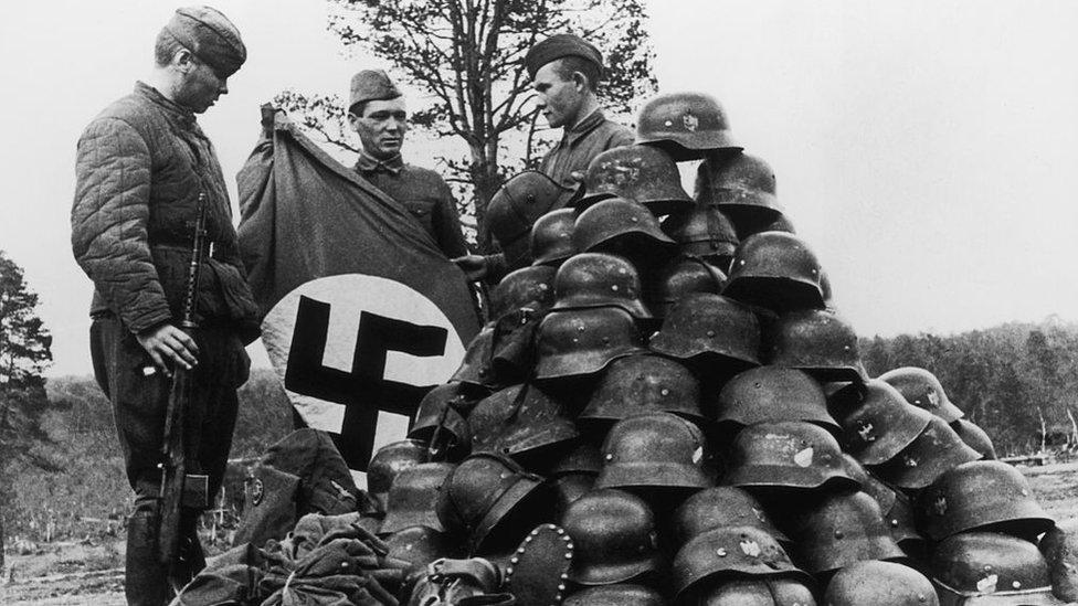 Soldados soviéticos apilan objetos capturados de sus enemigos alemanes en Murmansk, Rusia.