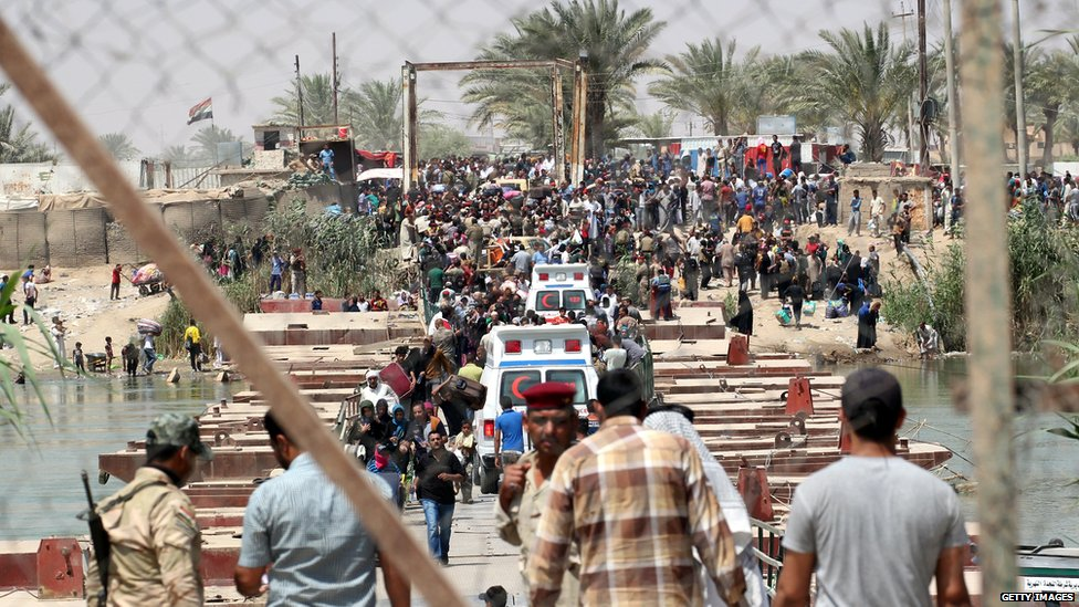 Iraqi security forces stand guard as residents from the city of Ramadi wait to cross into Baghdad