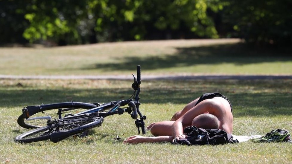 """A man sunbathes next to his bicycle in Regent""""s Park, London"""