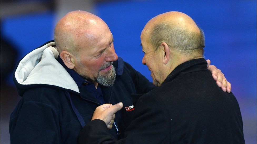 French Defence Minister Jean-Yves Le Drian (R) embraces Serge Lazarevic (L), France's last remaining hostage after landing at the Villacoublay military base near Paris, France on December 10, 2014.