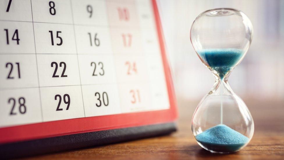 Reloj de arena frente a un calendario