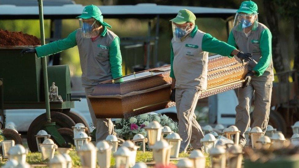 Coveiros levam caixão em cemitério de Brasília