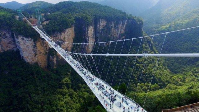 Visitors walk across a glass-floor suspension bridge in Zhangjiajie in southern China's Hunan Province Saturday, Aug. 20, 2016