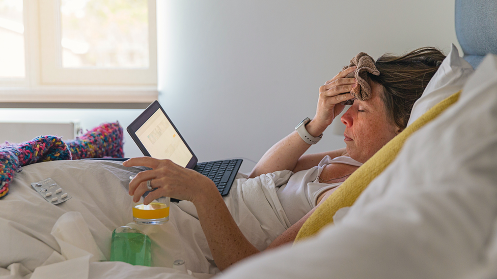 A woman in bed looking unwell watching a laptop